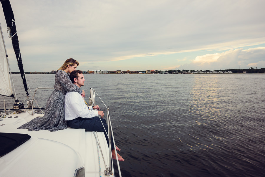 Newlyweds hugging and looking out over the water on a sailboat, Epic Pensacola Sunset Sailing, Lazzat Photography