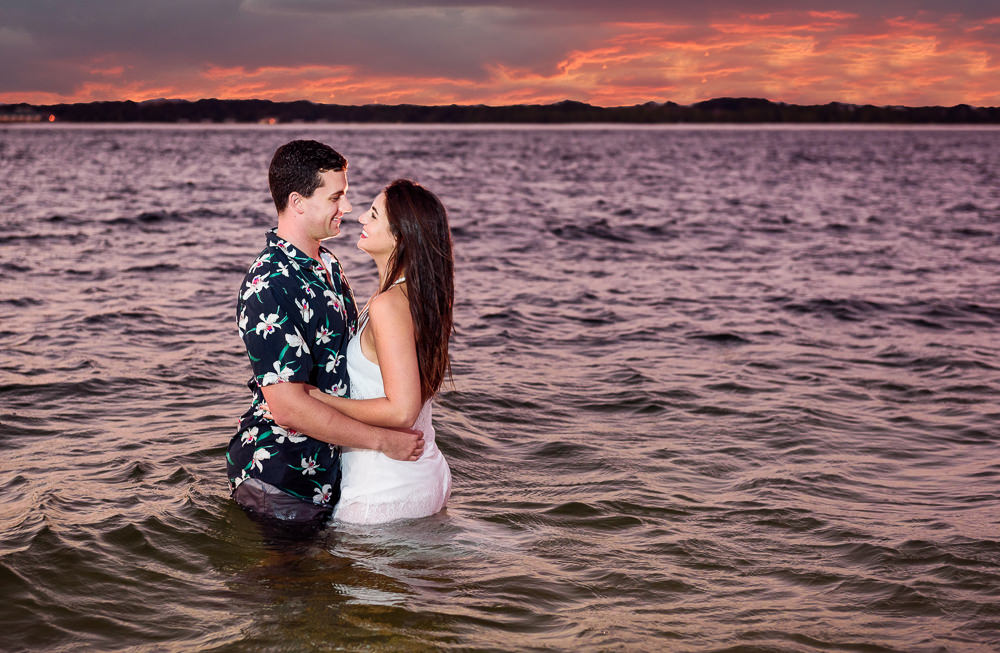Timber+Alec standing in the water facing each other and smiling with an epic sunset during their Ft. Pickens Sunset Engagement Session, Timber+Alec, Ft. Pickens Sunset Engagement Session, Pensacola engagement photographer, Pensacola engagement photo session, Pensacola engagement photos, Pensacola engagement photography, Lazzat Photography
