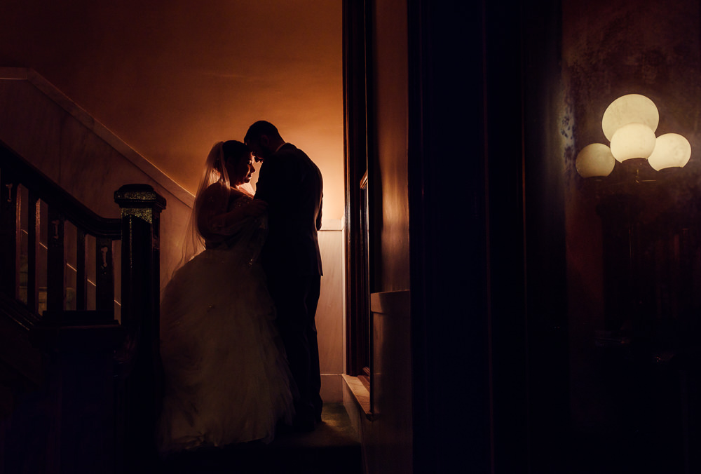 Bride and Groom dark romantic moment in stairwell, Downtown Pensacola Grand Hotel Wedding, Lazzat Photography, Florida wedding photographer