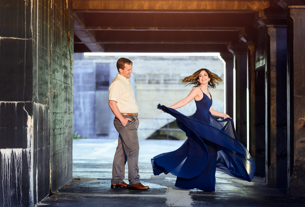 Woman spinning in her blue dress while man watches, Fun Engagement Session at Eden Garden and Fort Pickens, Lazzat Photography, engagement photos