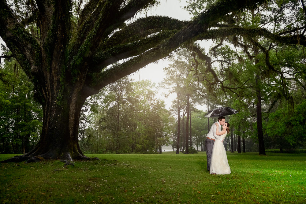 Couple hugging under umbrella in the rain, Fun Engagement Session at Eden Garden and Fort Pickens, Lazzat Photography, engagement photos
