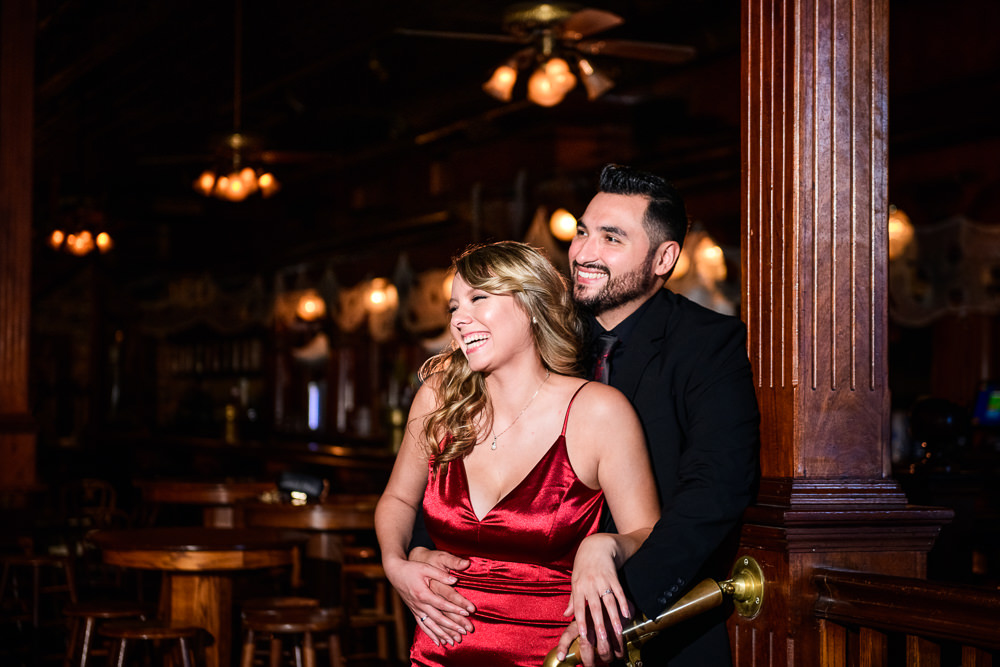 Couple laughing in Seville Quarter, New Orleans Inspired Engagement Session, Long red gown, Pensacola engagement photographer, Lazzat Photography