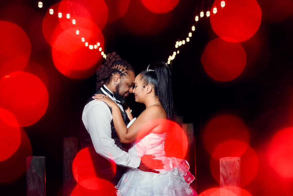 Bride and Groom forehead to forehead at night with red and white twinkle lights, Royal Red Destination Wedding, Florida wedding photographer, Lazzat Photography