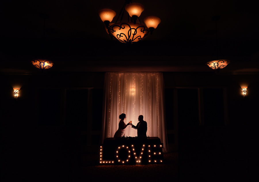 Silhouette of Bride and Groom cheers in front of LOVE light up sign, Scenic Hills Country Club, Catholic country club wedding, Pensacola Florida, Lazzat Photography
